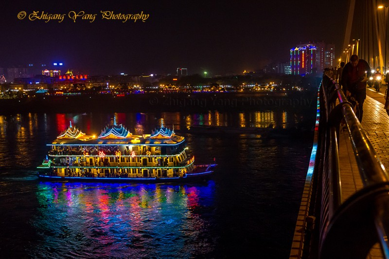 Sightseeing boat passing Xishuangbanna Bridge on Lancang River